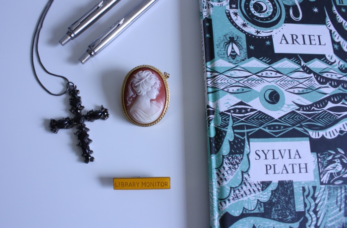 a black cross necklace, camera brooch and the book Ariel by Sylvia Plath