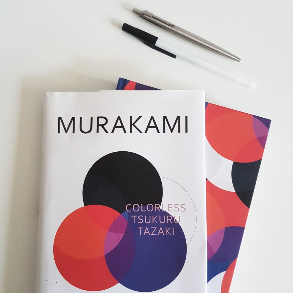book cover of murukami's colorless tzukuru tazaki on a table beside pens