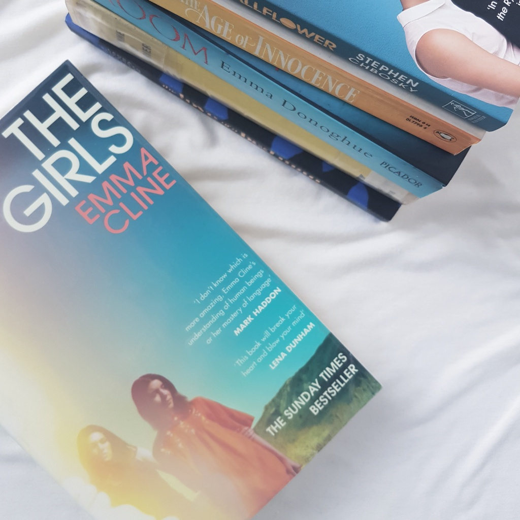 book cover of the girls by cline beside other blue and yellow books