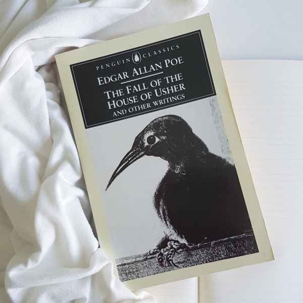 a black crow on Edgar Allan Poe's story collection on top of a white sheet