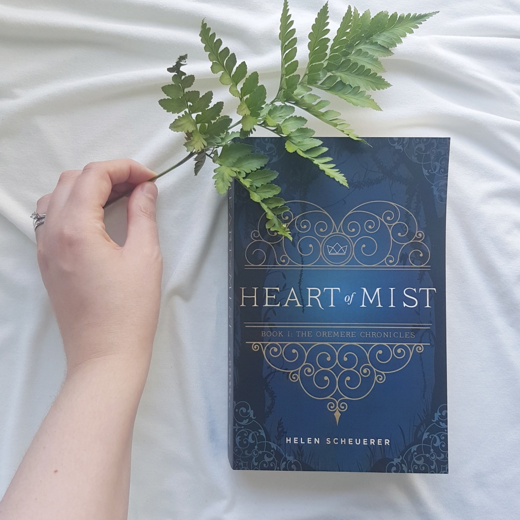 A hand holds a fresh fern leaf over the blue cover of Heart of Mist