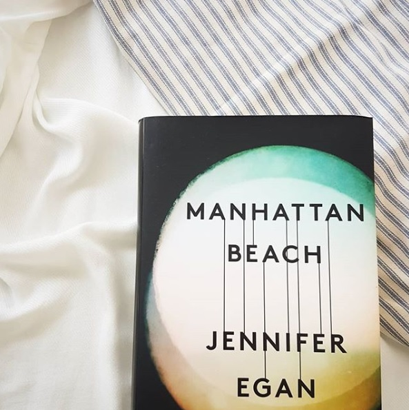 the hardback cover of Manhattan Beach by Jennifer Egan on a striped bedspread