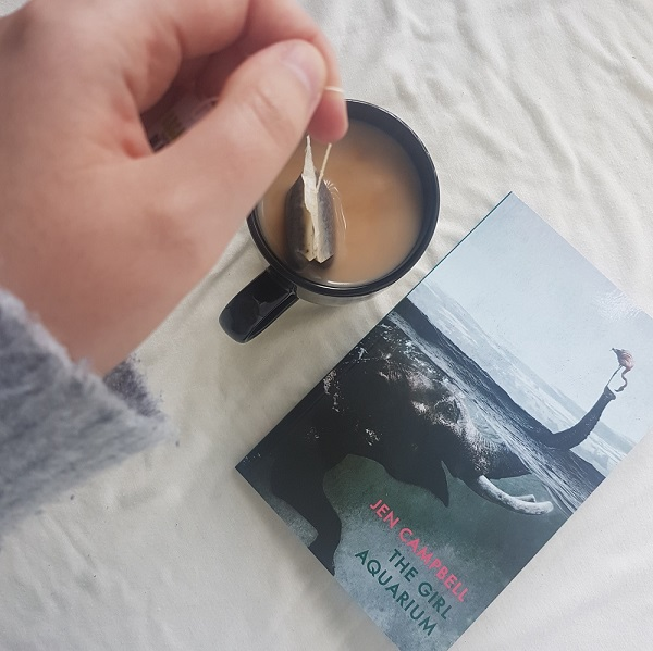 Book The Girl Aquarium by Jen Campbell on a white blanket beside a hand holding a teabag over a tea cup