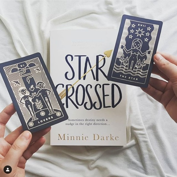 Star-Crossed, a white book cover with black typeface. Two hands holding two tarot cards hover over the book: the cards are The Lovers and The Star